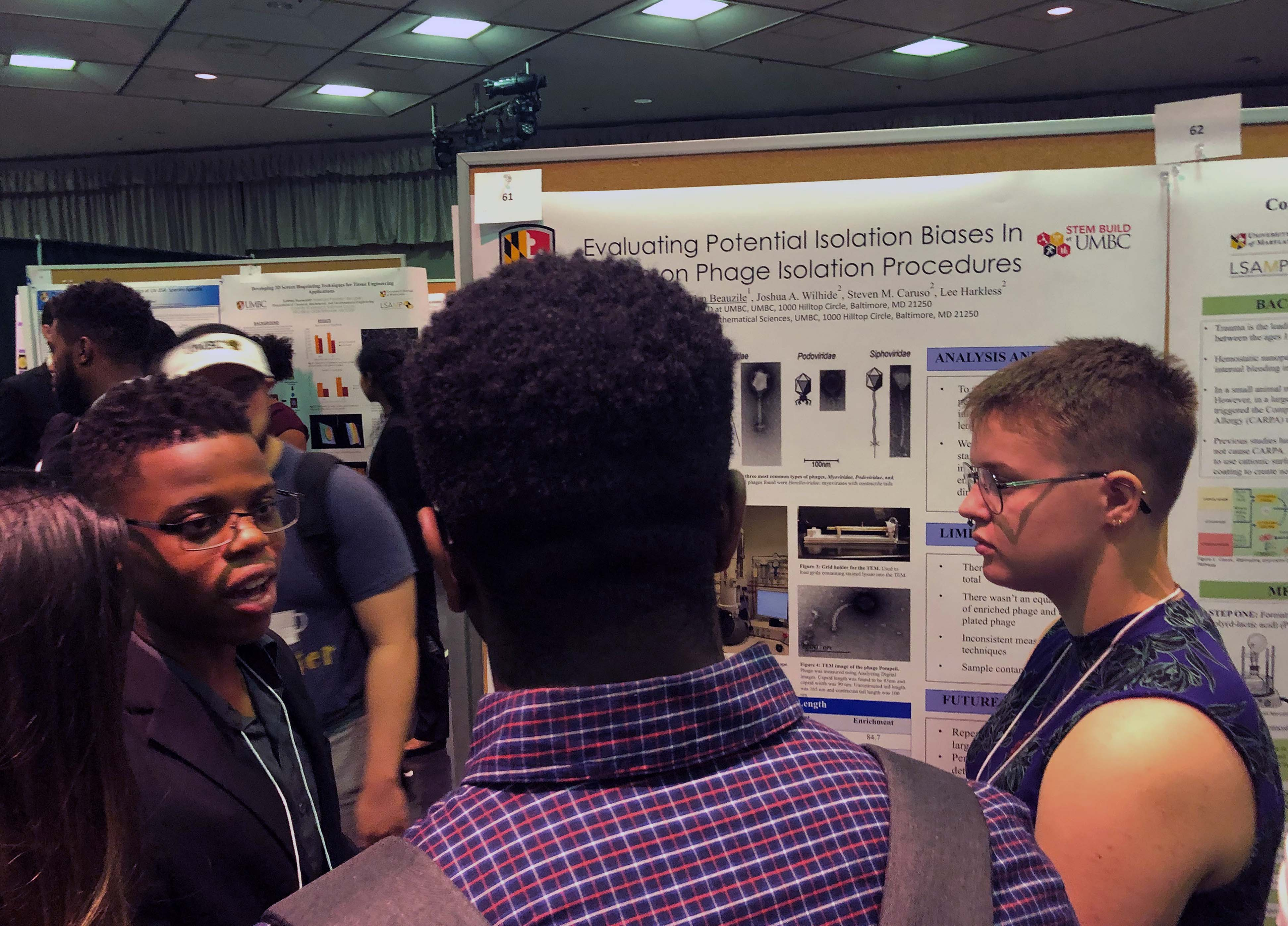 UMBC BUILD Trainees explain their research poster to guests at the Summer Undergraduate Research Fest